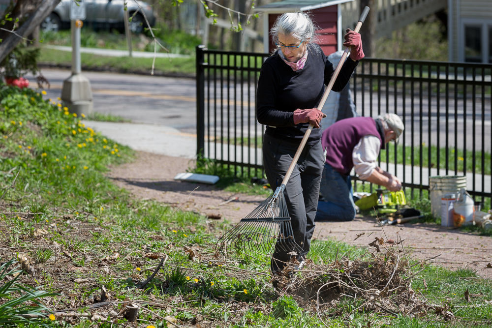 Woman rakes leaves at park