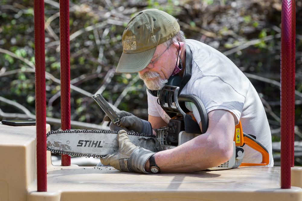Man sharpens chainsaw at park