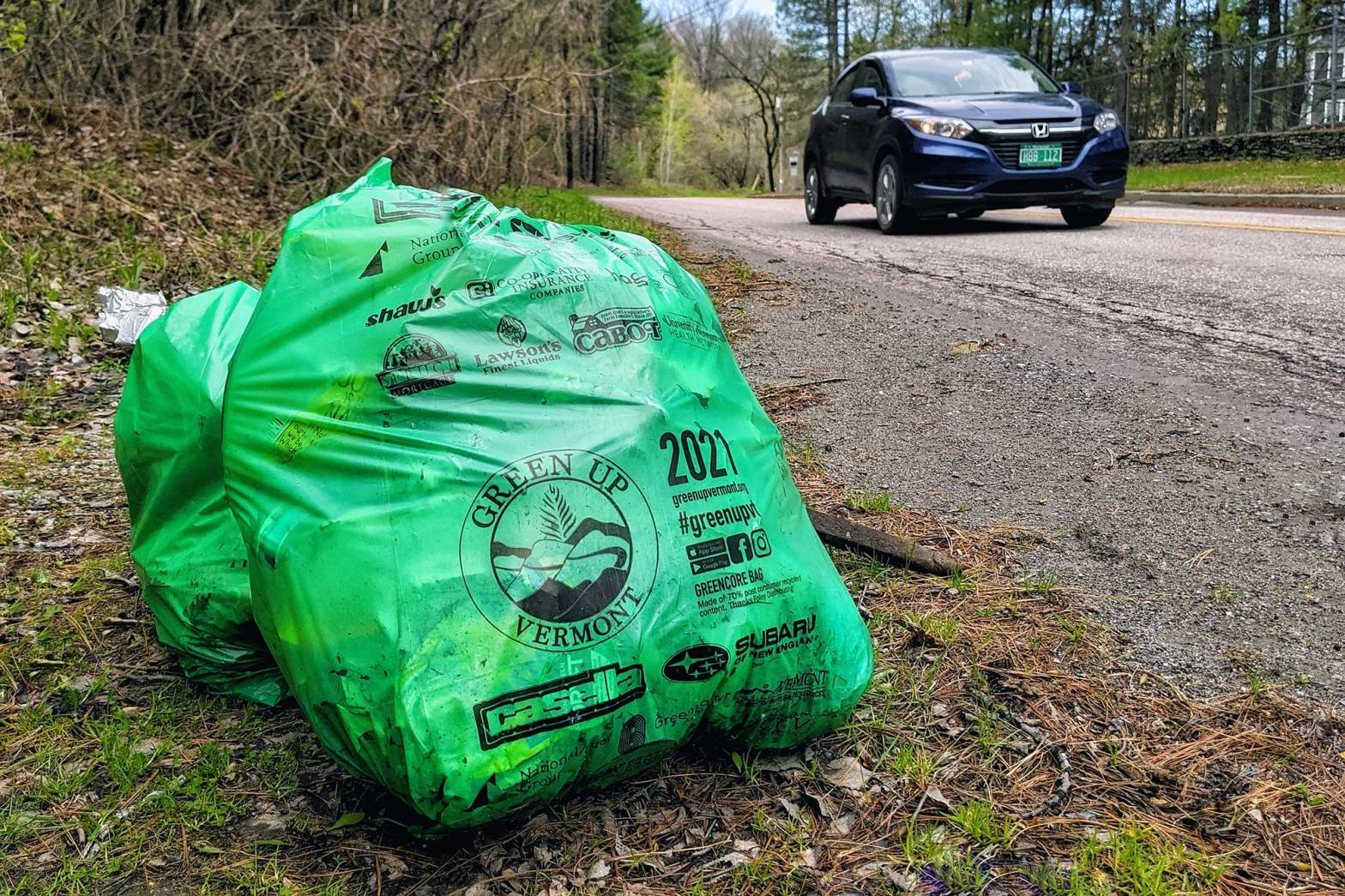 Full green trash bags on the side of a street