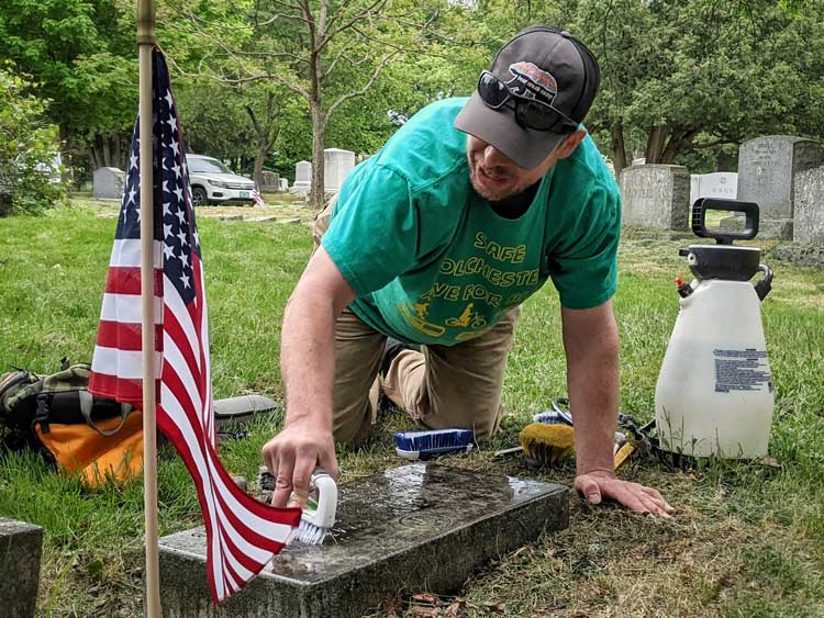 Man cleans moss and lichen off a grave stone in a cemetery
