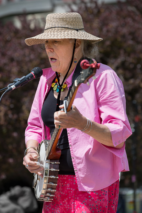 Musician sings and plays banjo outside on a sunny day