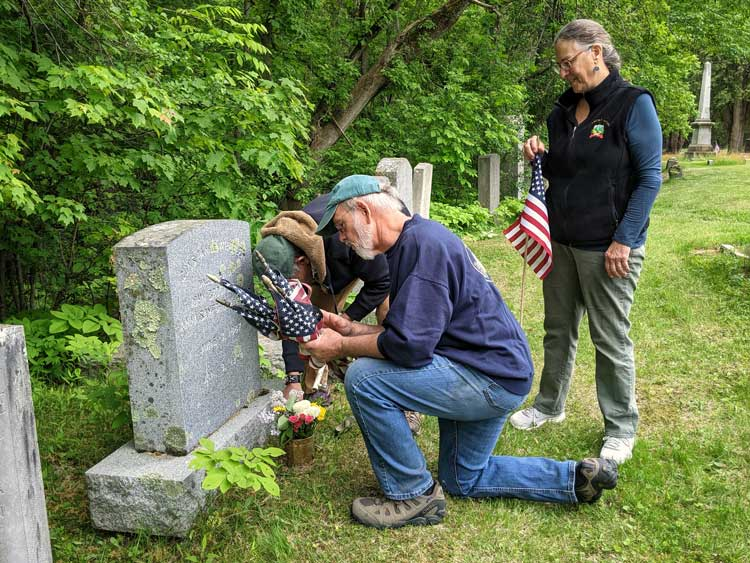 3 people place flags at a gravestone in Greenmount Cemetery